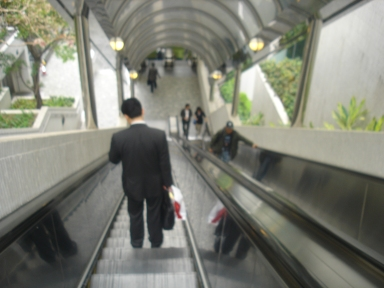 Man in a suit going down the escalator from the park at Central